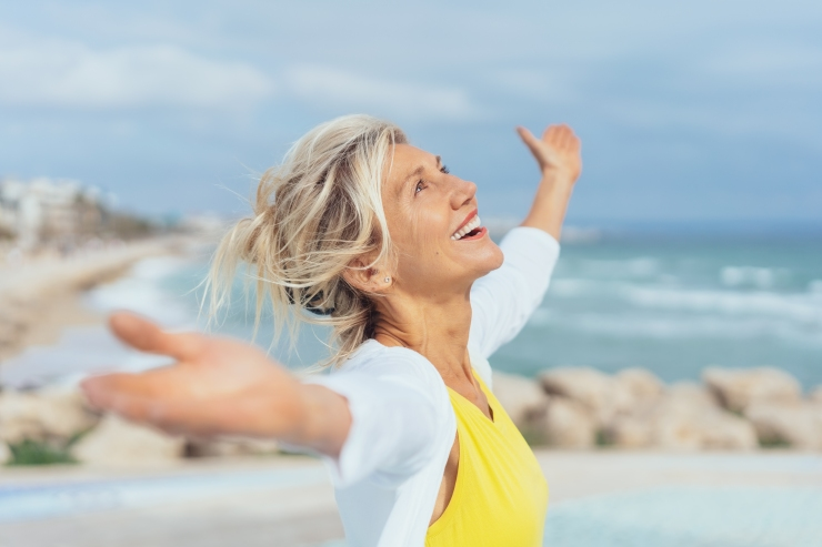 Mature woman, happy, on the beach; menopause fitness
